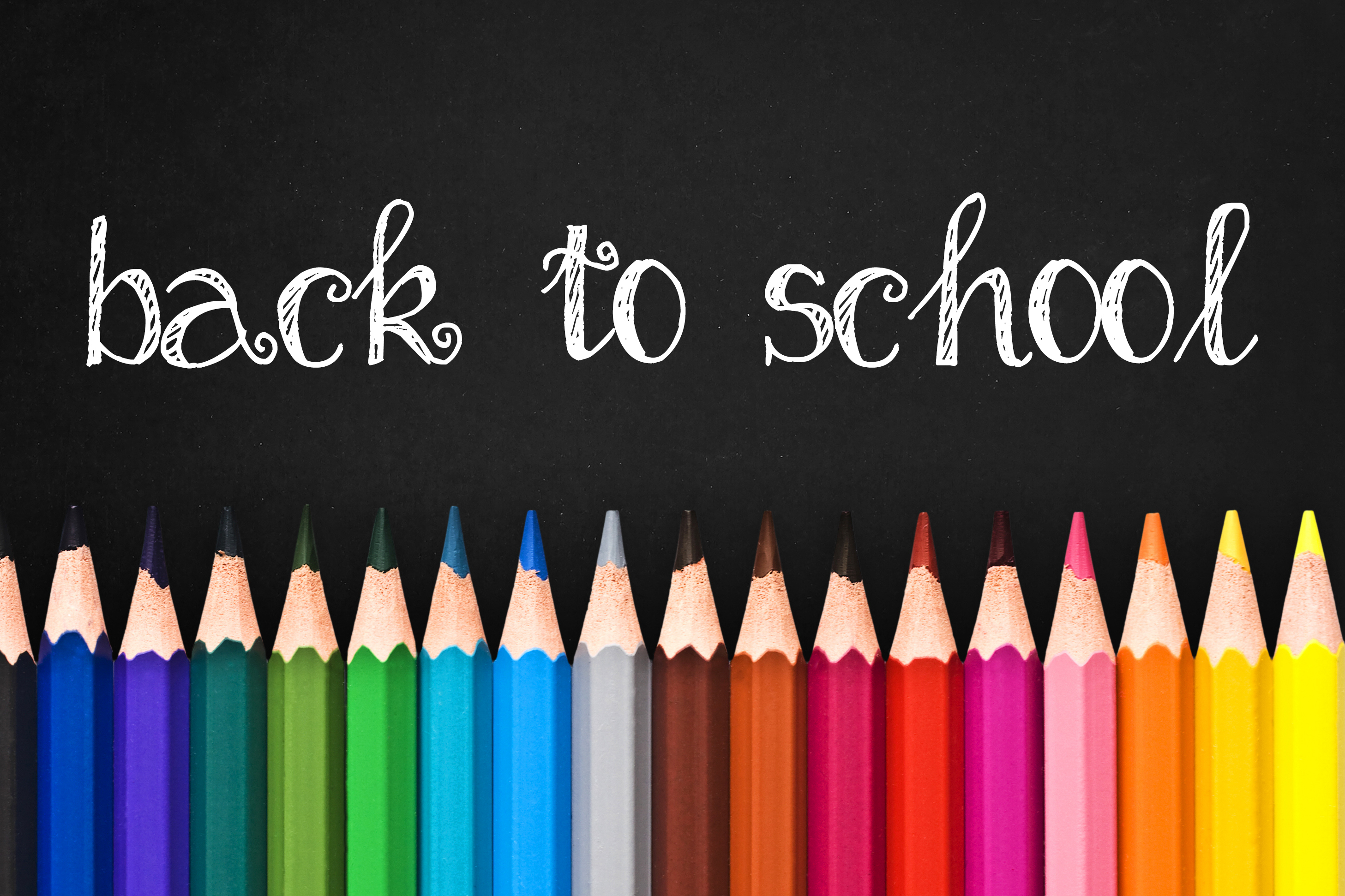 Back to school written on black chalkboard background with colorful wooden pencils
